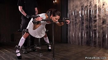 Hot brunette slave Kacie Castle in red panties and hot dress in metal device bondage waits for master