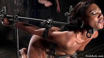 Hanged for ankles with hands tied up behind back ebony slut Chanell Heart gets whipped then in metal device bondage whipped and feet caned