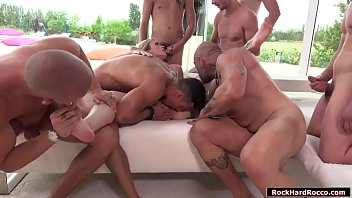 Slut blonde is on the couch sitting and suddenly a lot of naked guys go to her.They start licking her pussy and they let her throat their bigcocks.After that,they fuck her ass and pussy simultaneously while shes sucking other big cocks.