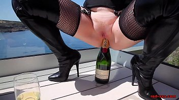 British beauty Red XXX fucking her hairless pussy with a bottle outdoors
