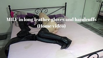Handcuffed woman dressed in leather opera gloves, overknee boots, hood