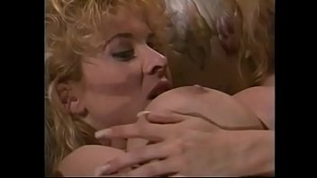 Big haired blonde Stephanie DuValle nice tits is fucked by dude with a ponytail on couch while his wife Lynden Johnsonwith huge melons watching