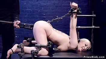 Blonde slave is locked in metal device bondage on her knees and pussy and ass toyed by master