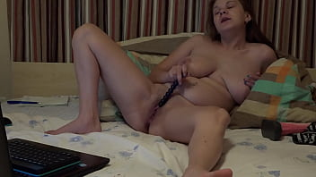 A busty girl in front of a webcam fucks a hairy vagina with sex toys and fingering the clitoris.