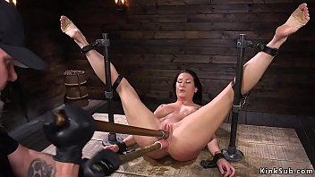 Master shackles busty toned brunette slave Ariel X to the wooden wall and vibrates her then in metal device double penetration toys her
