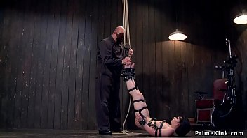 Baldheaded master Sgt Major suspends hot strapped brunette slut for ankles then shackles her on the floor and fingers and whips her