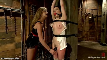 Strapped to wooden post gagged brunette lesbian slave Juliette March is whipped by dominatrix Felony then spanked and ass fucked with strapon